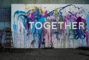A wall splashed with paint and the word Together